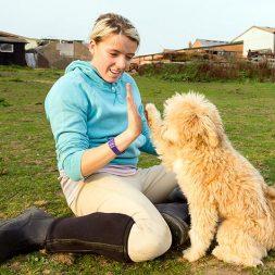 woman teaching a dog hand commands