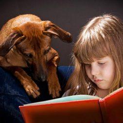 child and dog reading