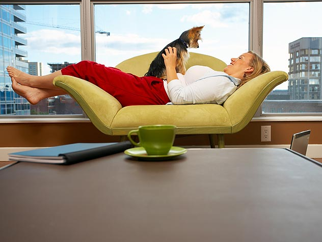 woman and dog laying on a couch