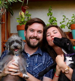man and woman holding dogs