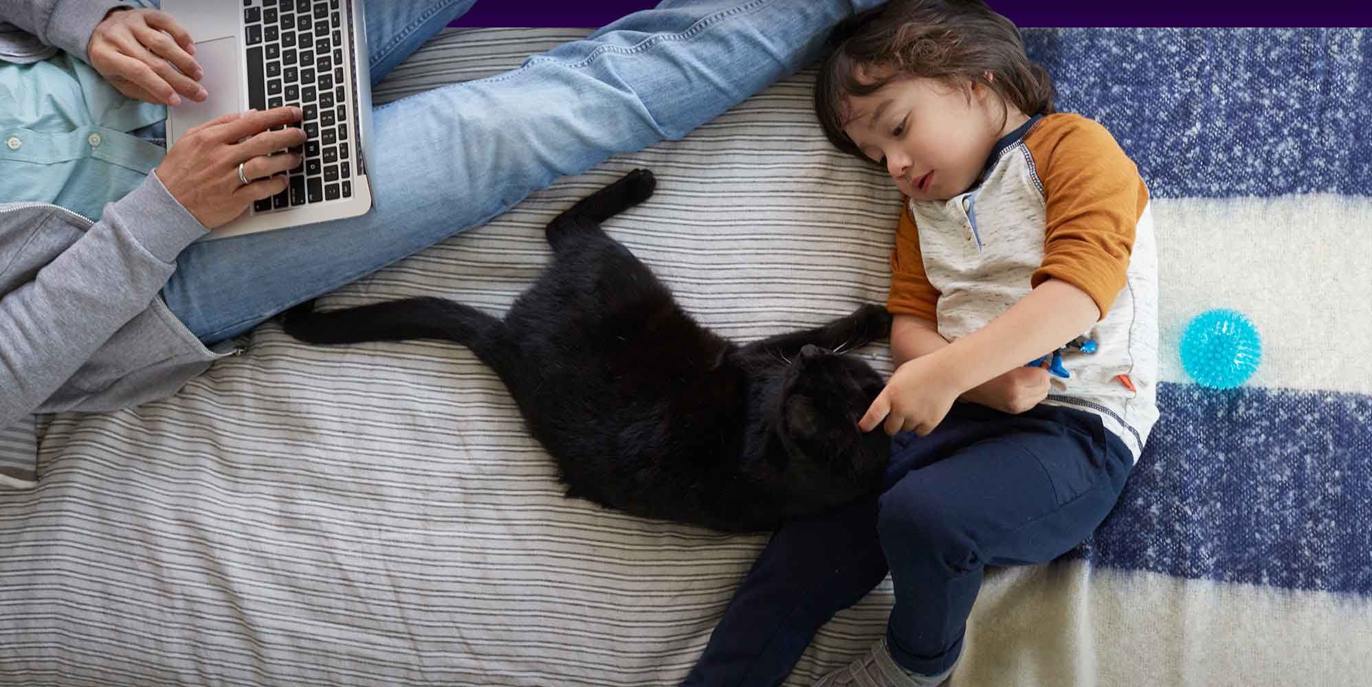 A child laying on the bed with their black cat.