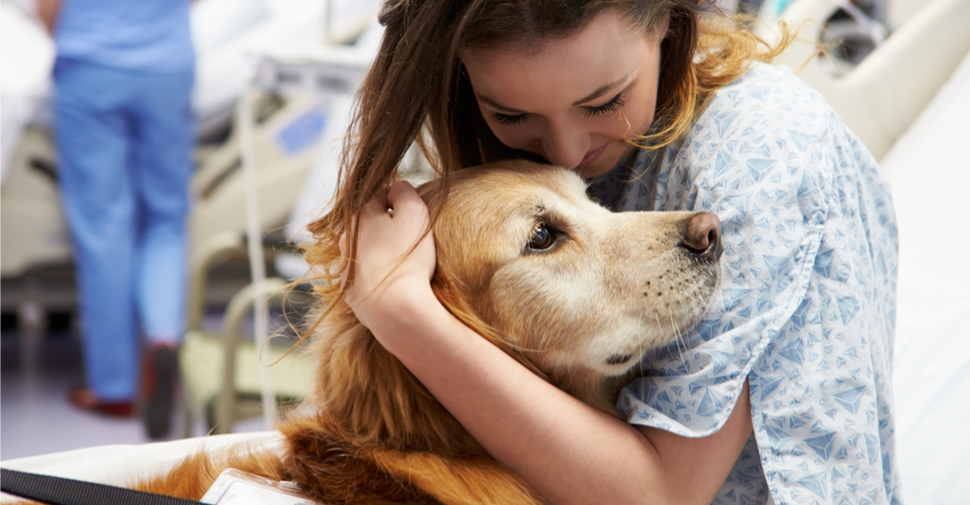 girl in the hospital hugging a dog