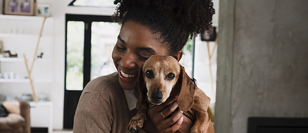 woman hugging a brown dog